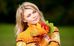 lovely blonde woman in yellow sweater holding leaves